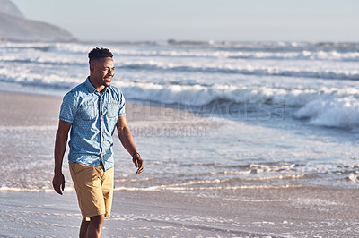 Buy stock photo Shot of a handsome young man enjoying a day at the beach