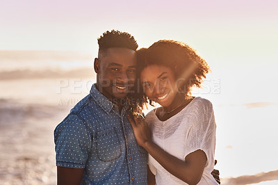 Buy stock photo Portrait of an affectionate young couple enjoying a day at the beach