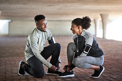 Buy stock photo Full length shot of a young couple fastening their shoelaces listening during their workout in the city
