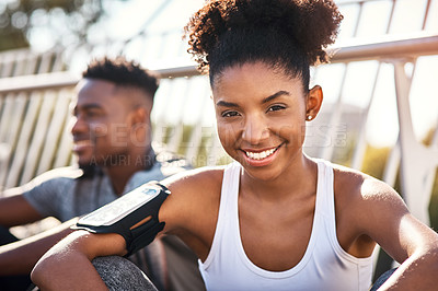 Buy stock photo Cropped portrait of an attractive young woman exercising outdoors in the city with her boyfriend in the background