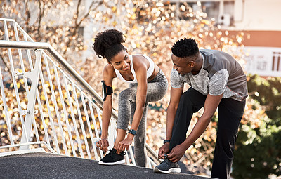Buy stock photo Cropped shot of a young couple fastening their shoelaces during their workout in the city