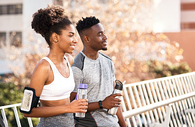 Buy stock photo Cropped shot of a young couple taking a break for some water while exercising outdoors in the city