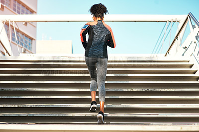 Buy stock photo Rearview shot of an unrecognizable young woman exercising outdoors in the city