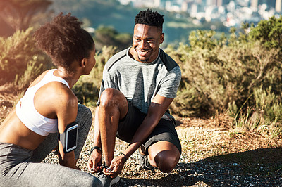 Buy stock photo Cropped shot of a young couple fastening their shoelaces before beginning their run