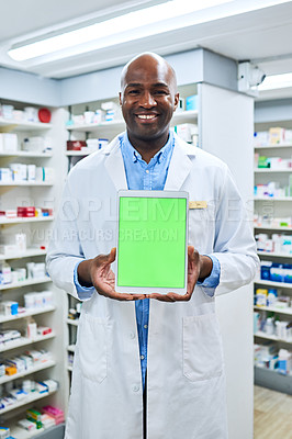 Buy stock photo Shot of a pharmacist holding up a digital tablet in a chemist