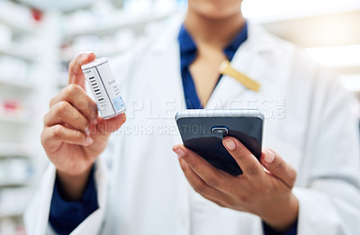 Buy stock photo Cropped shot of a pharmacist using her cellphone while holding medication