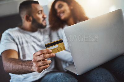 Buy stock photo Cropped shot of an affectionate young couple doing some online shopping at home