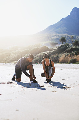 Buy stock photo Shot of a sporty young couple tying their shoelaces while out for a run along the beach