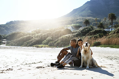 Buy stock photo Shot of a sporty young couple taking a break with their dog while exercising at the beach
