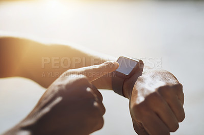 Buy stock photo Closeup shot of an unrecognizable man checking his smartwatch while exercising outdoors
