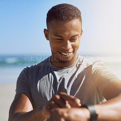 Buy stock photo Shot of a sporty young man checking his smartwatch while exercising outdoors
