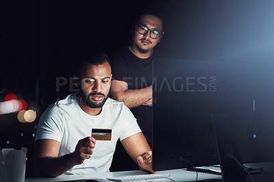 Buy stock photo Shot of two businessmen using a credit card while working on a computer in an office at night