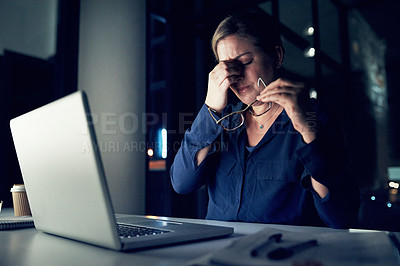 Buy stock photo Shot of a young businesswoman looking stressed out while working on a laptop in an office at night