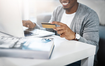 Buy stock photo Cropped shot of a young man using his laptop to shop online at home