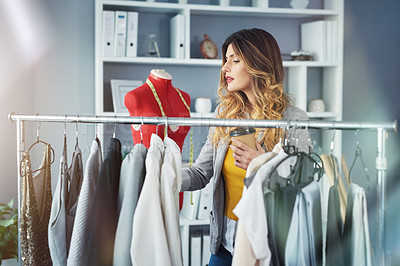 Buy stock photo Shot of a young woman going through a rack of clothing in her design studio