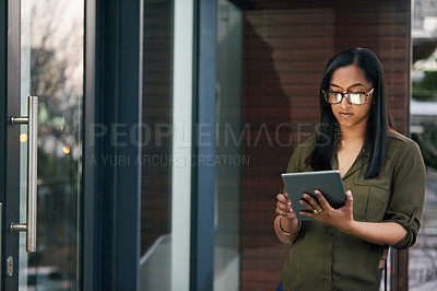 Buy stock photo Shot of a young businesswoman using a digital tablet outside on the balcony of an office
