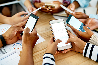Buy stock photo Cropped shot of a group of students using their mobile phones while studying together
