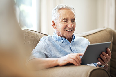 Buy stock photo Cropped shot of a senior man using his tablet while sitting on the sofa at home