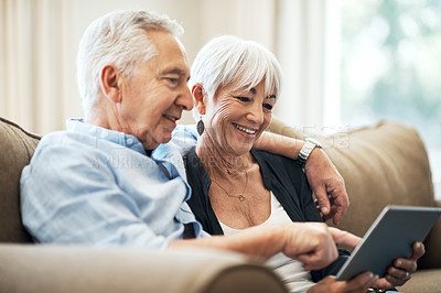 Buy stock photo Cropped shot of an affectionate senior couple using their tablet while sitting on the sofa at home