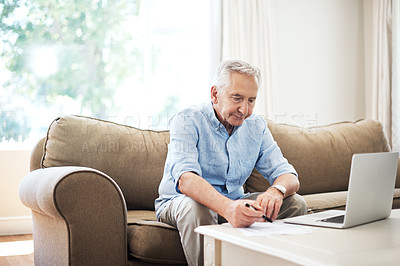 Buy stock photo Cropped shot of a senior man going through his finances while sitting on the sofa at home