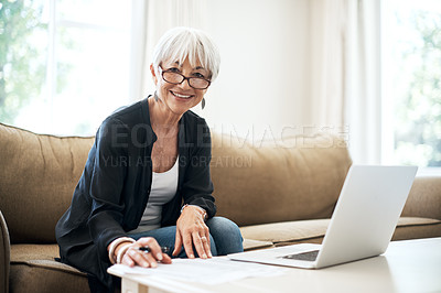 Buy stock photo Cropped portrait of a senior woman going through her finances while sitting on the sofa at home