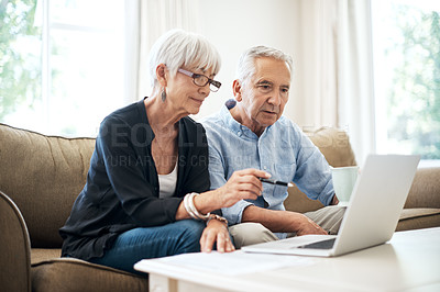 Buy stock photo Cropped shot of a senior couple going through their finances while sitting on the sofa at home