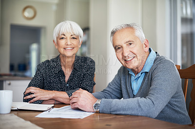 Buy stock photo Cropped portrait of a senior couple going through their finances while sitting at the dining room table