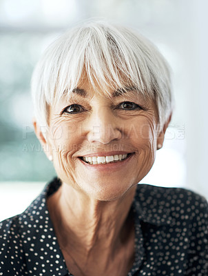 Buy stock photo Cropped portrait of a senior woman sitting in her living room at home