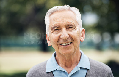 Buy stock photo Cropped portrait of a senior man standing outside on a summer's day