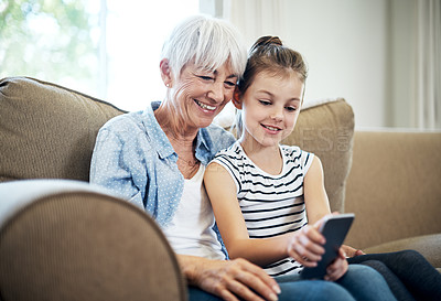 Buy stock photo Shot of an adorable little girl using a mobile phone with her grandmother at home