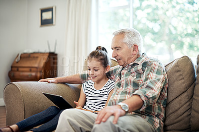 Buy stock photo Shot of an adorable little girl using a digital tablet with her grandfather at home