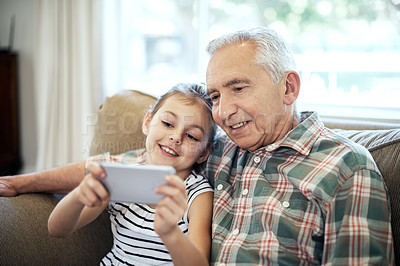 Buy stock photo Shot of an adorable little girl taking a selfie with her grandfather at home