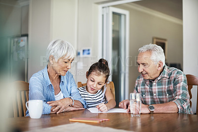 Buy stock photo Shot of a senior woman helping her granddaughter with a creative project