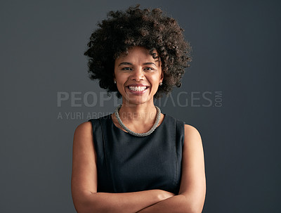 Buy stock photo Studio shot of a young attractive businesswoman posing against a dark background