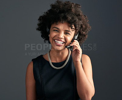 Buy stock photo Studio shot of a young attractive businesswoman talking to a customer using a headset while posing against a dark background