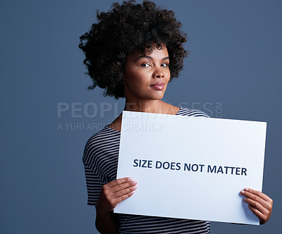 """Buy stock photo Studio shot of an attractive young woman holding a placard with the words """"size does not matter"""" on it"""