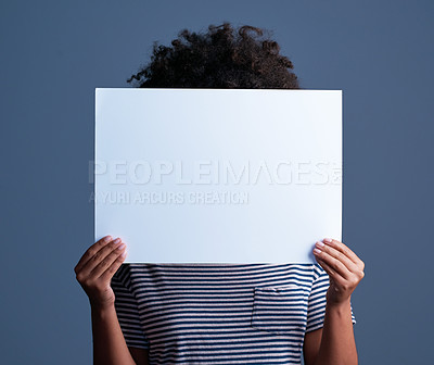 Buy stock photo Studio shot of a young woman holding a blank placard against a blue background