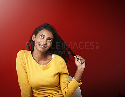 Buy stock photo Studio portrait of a beautiful young woman looking thoughtful against a red background