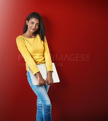 Buy stock photo Studio portrait of an attractive young woman holding a laptop against a red background