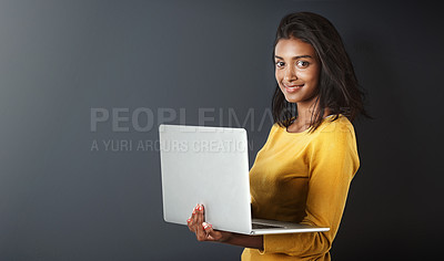Buy stock photo Studio portrait of an attractive young woman using a laptop against a gray background