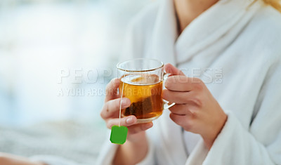Buy stock photo Cropped shot of an unrecognizable young woman relaxing at home with a glass of tea