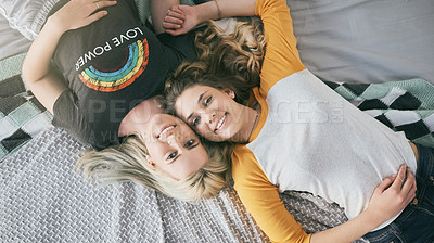 Buy stock photo High angle shot of two friends lying on a bed together