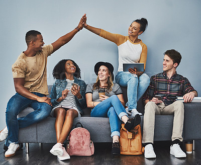 Buy stock photo Studio shot of a young man and woman giving each other a high five while hanging out with their friends