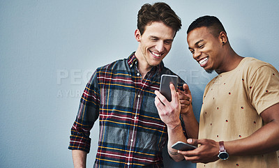 Buy stock photo Studio shot of two young men using a mobile phone together against a gray background