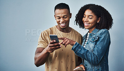 Buy stock photo Studio shot of a young man and woman using a mobile phone together against a gray background