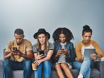 Buy stock photo Studio shot of young people sitting on a sofa and using wireless technology against a gray background