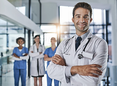 Buy stock photo Portrait of a confident young doctor working in a hospital with his colleagues in the background