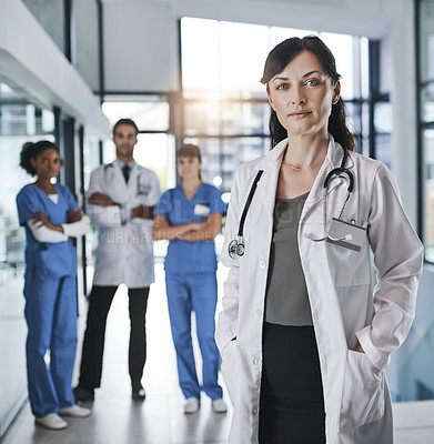 Buy stock photo Portrait of a confident mature doctor working in a hospital with her colleagues in the background