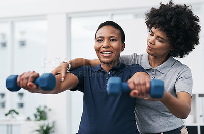 Buy stock photo Shot of a physiotherapist helping a patient work through her recovery with weights