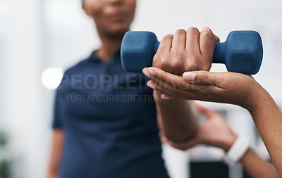 Buy stock photo Closeup shot of a physiotherapist helping a patient work through her recovery with weights